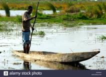 local-bayei-people-in-the-tradiional-mokoro-dugout-boat-okavango-delta-okavango-swamp-botswana-XD7EPK